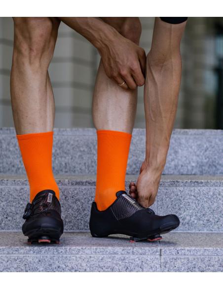 nogi kolarza na schodach podczas zapinania BOA na butach Suplest w pomarańczowych skarpetkach kolarskich