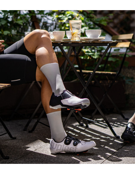 kolarz w srebrno-szarych skarpetach rowerowych podczas przystanku na kawę