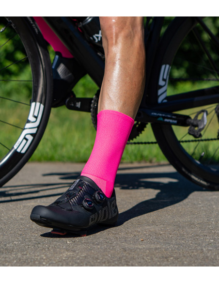 shaved cyclists leg with pink fluorescent cycling socks
