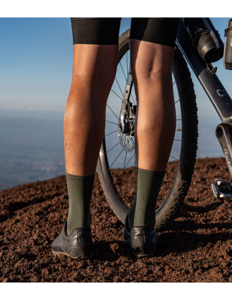 cyclist wearing khaki Luxa cycling socks and stands on volcanic dust. Designed to adventure gravel rides.