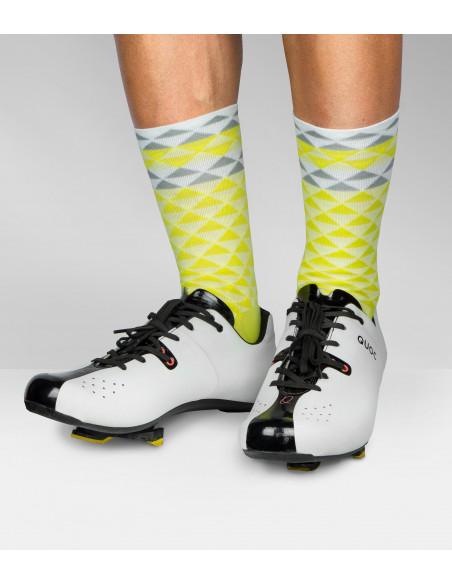 Nogi kolarza z butami Quoc i żółtymi skarpetkami rowerowymi Luxa