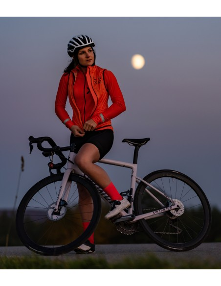 women wears orange cycling kit with reflective gilet