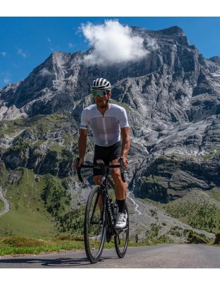 ubrany w strój kolarski Luxa kolarz jedzie po szosie w górach w skarpetkach koloru czarnego