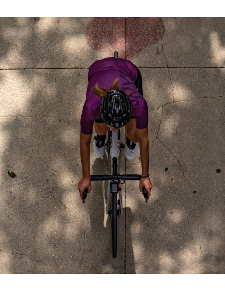 cyclist riding in Catania with purple cycling kit and socks in the same color