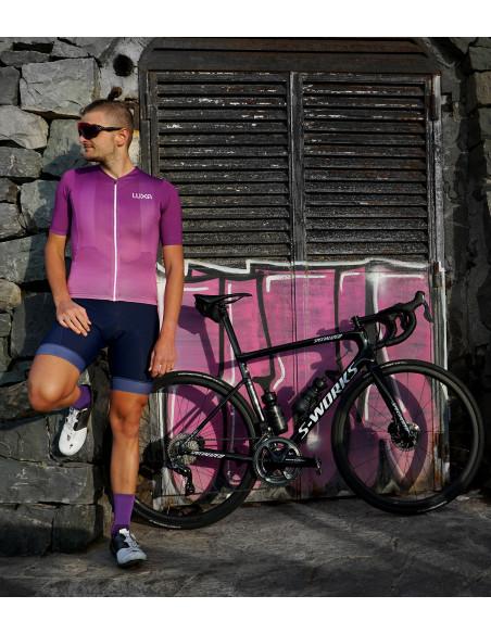 Kolarz w fioletowym stroju kolarskim Aurora z rowerem i butami Specialized