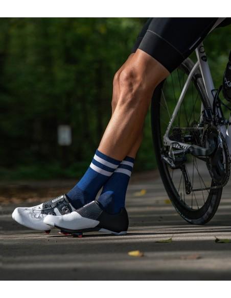 kolarz stoi oparty o rower ubrany w granatowe skarpetki kolarskie Luxa Navy Night