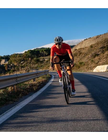 Całe zabarwione na czerwono elastyczne włókna skarpetek kolarskich na nodze kolarza jadącego po Sycylijskiej szosie.