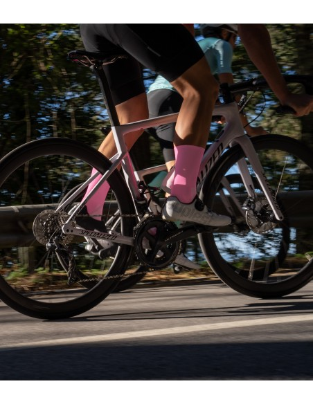 kolarz na szosie w butach Suplest i w całych różowych skarpetkach rowerowych marki Luxa