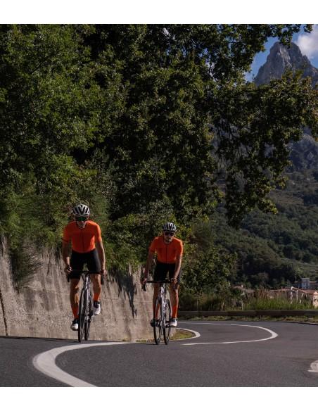 dwóch kolarzy jadą ubrani w pomarańczowe koszulki przeznaczone na letnie upały