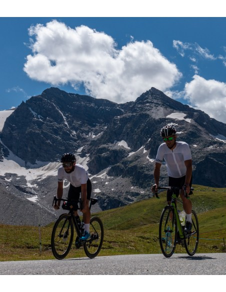 two friends are riding through the mountains in Italy (col de Nivolet) and they are wearing 'born to climb' cycling socks