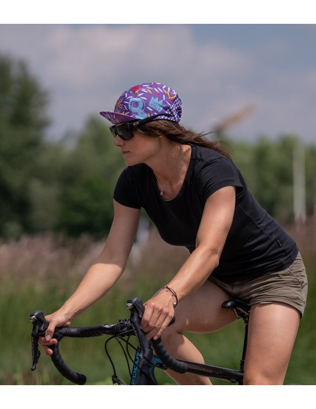 woman riding and wearing girl power cycling cap in violet color