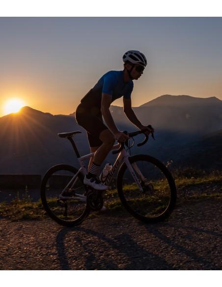kolarz w w skarpetkach rowerowych Luxa jedzie przy zachodzącym słońcu