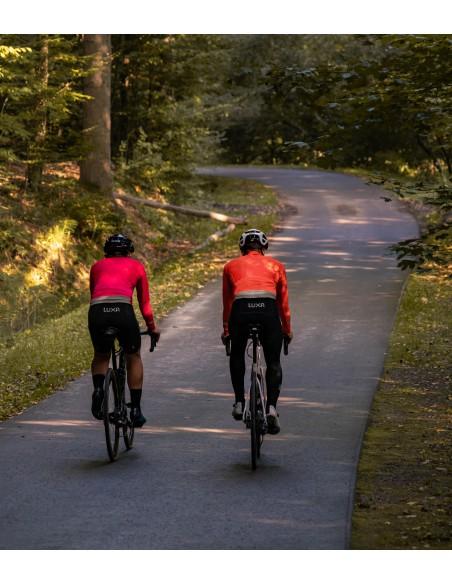 dwóch kolarzy jedzie szosą w lesie ubrani w ciepłe bluzy polskiej produkcji