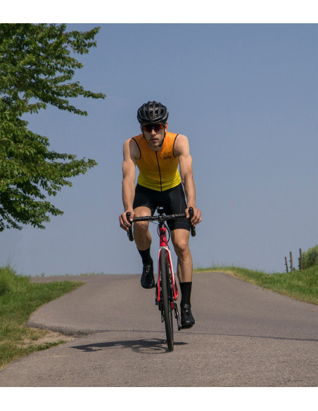 Cyclist training hard and wear orange sleeveless cycling jersey