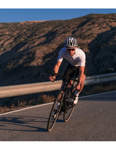Sierra Nevada switchbacks during the sunset. Cyclist wear white Secret Luxa kit without logo and no prints