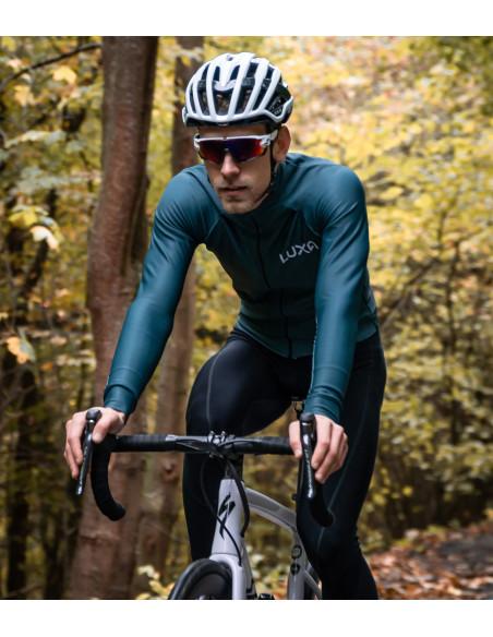 Ubrany na zielono kolarz w czasie jesiennej jazdy rowerem po lesie na szosie.