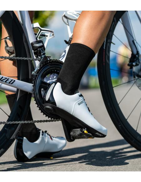 Noga kolarza z rowerem i butach Quoc z czarnymi skarpetkami
