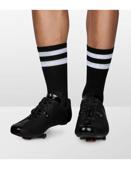 cyclists leg with black socks with stripes and quoc road shoes