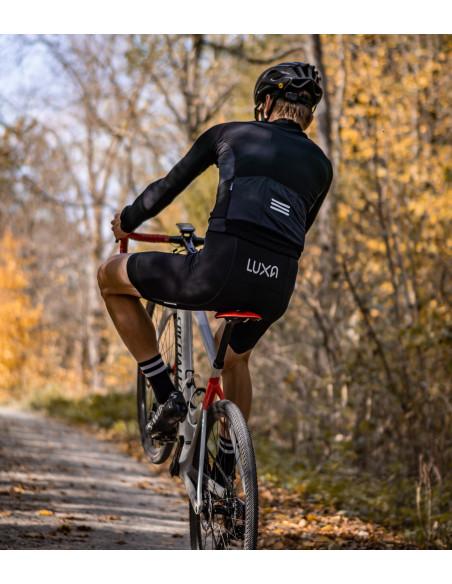 kolarz jedzie grawelem na jednym kole przez las ubrany w polski strój kolarski Luxa