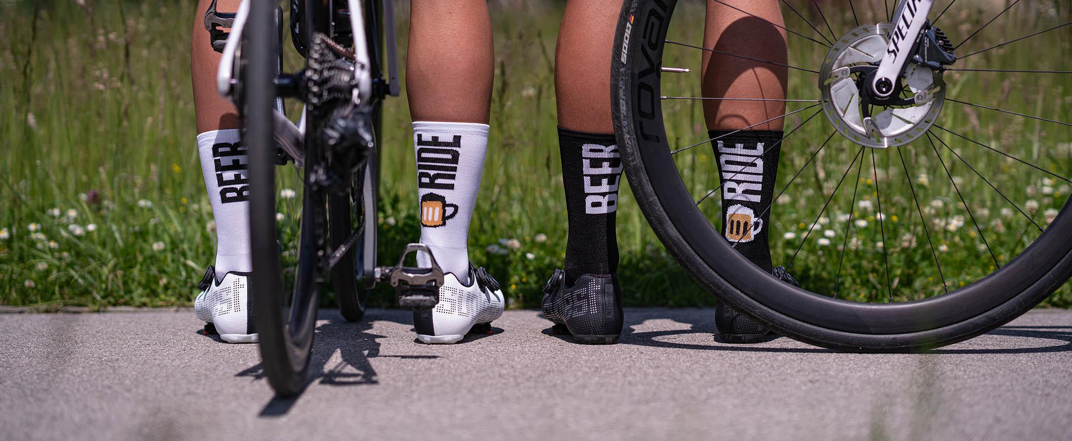 dwóch kolarzy stoją z rowerami Specialized ubrani w śmieszne i zabawne skarpetki rowerowe z napisami 'beer ride' z tyłu nogi