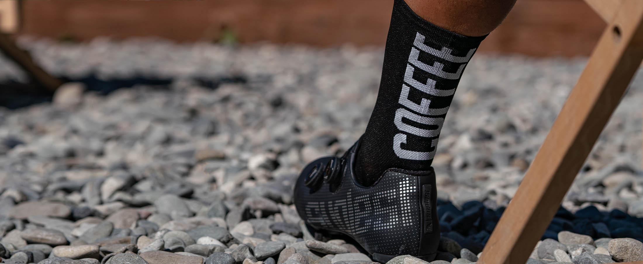 stopa kolarza w odpowiednich treningowych skarpetkach z napisem coffee ride i czarnymi butami szosowymi Suplest