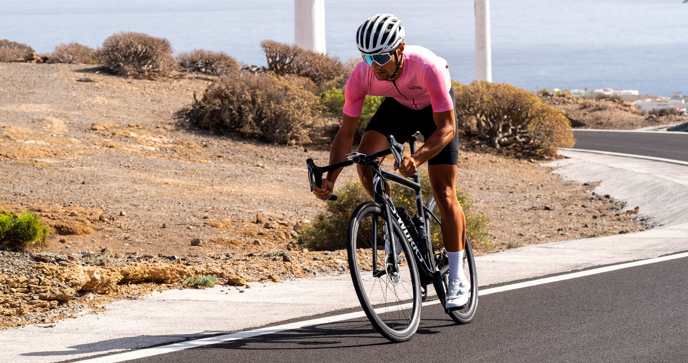 Road cyclist in pink Luxa jersey and black bib shorts