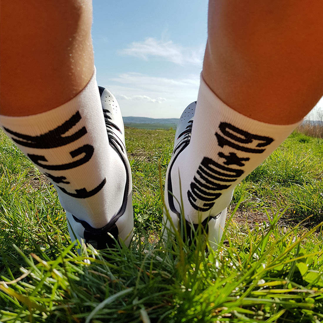 cyclist on the grass wearing fck covid-19 socks