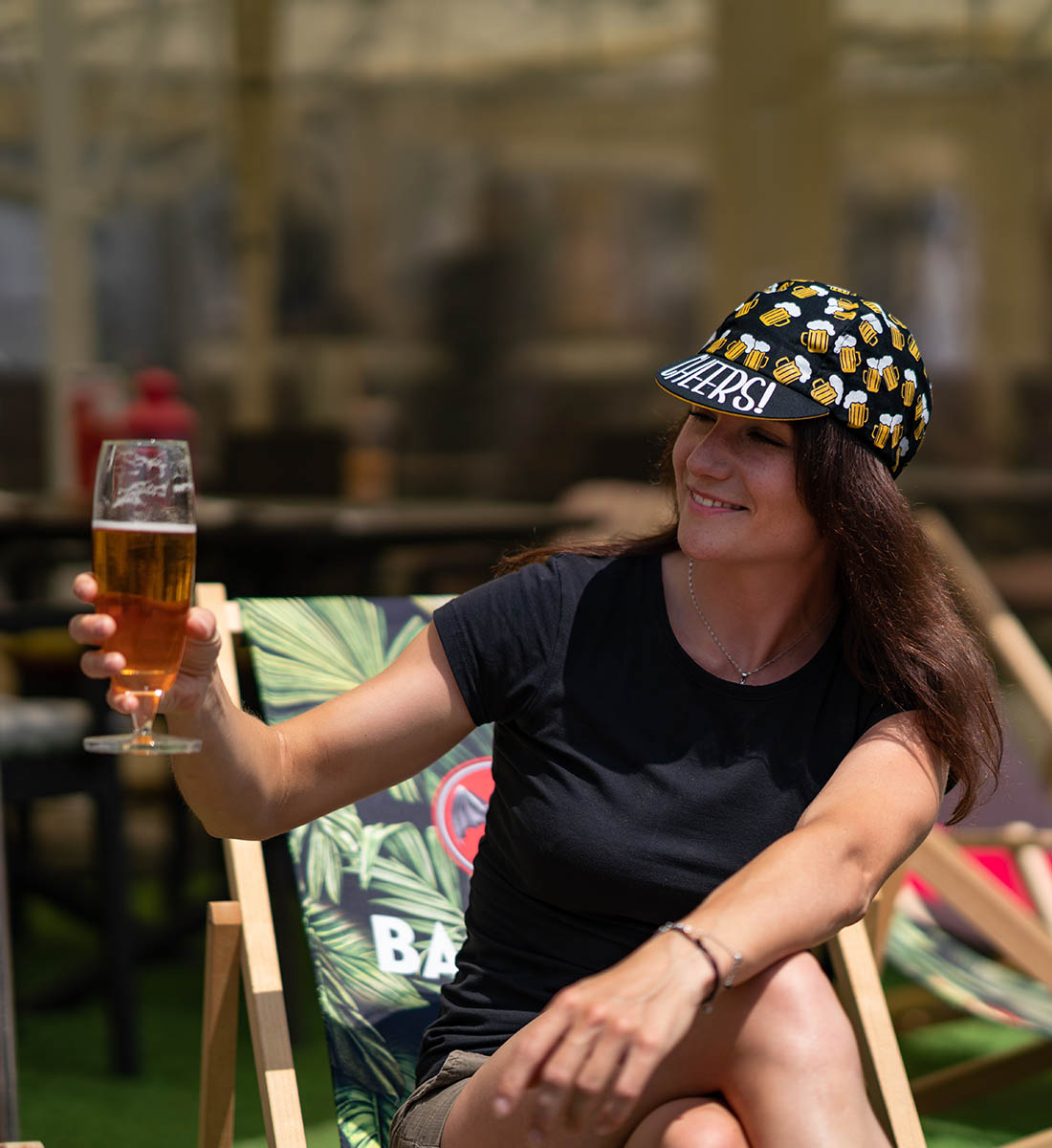 kobieta trzyma piwo bezalkoholowe i nosi piwną czapeczkę 'beer ride' z napisem 'cheers' od góry daszku