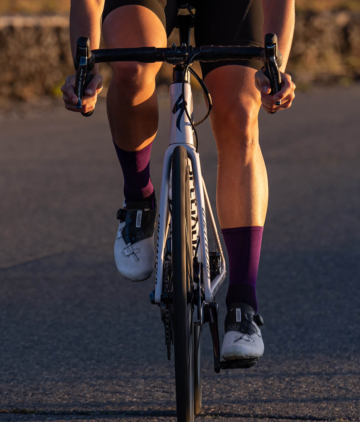 two cyclists during sunrise ride and one of them wear Luxa purple socks
