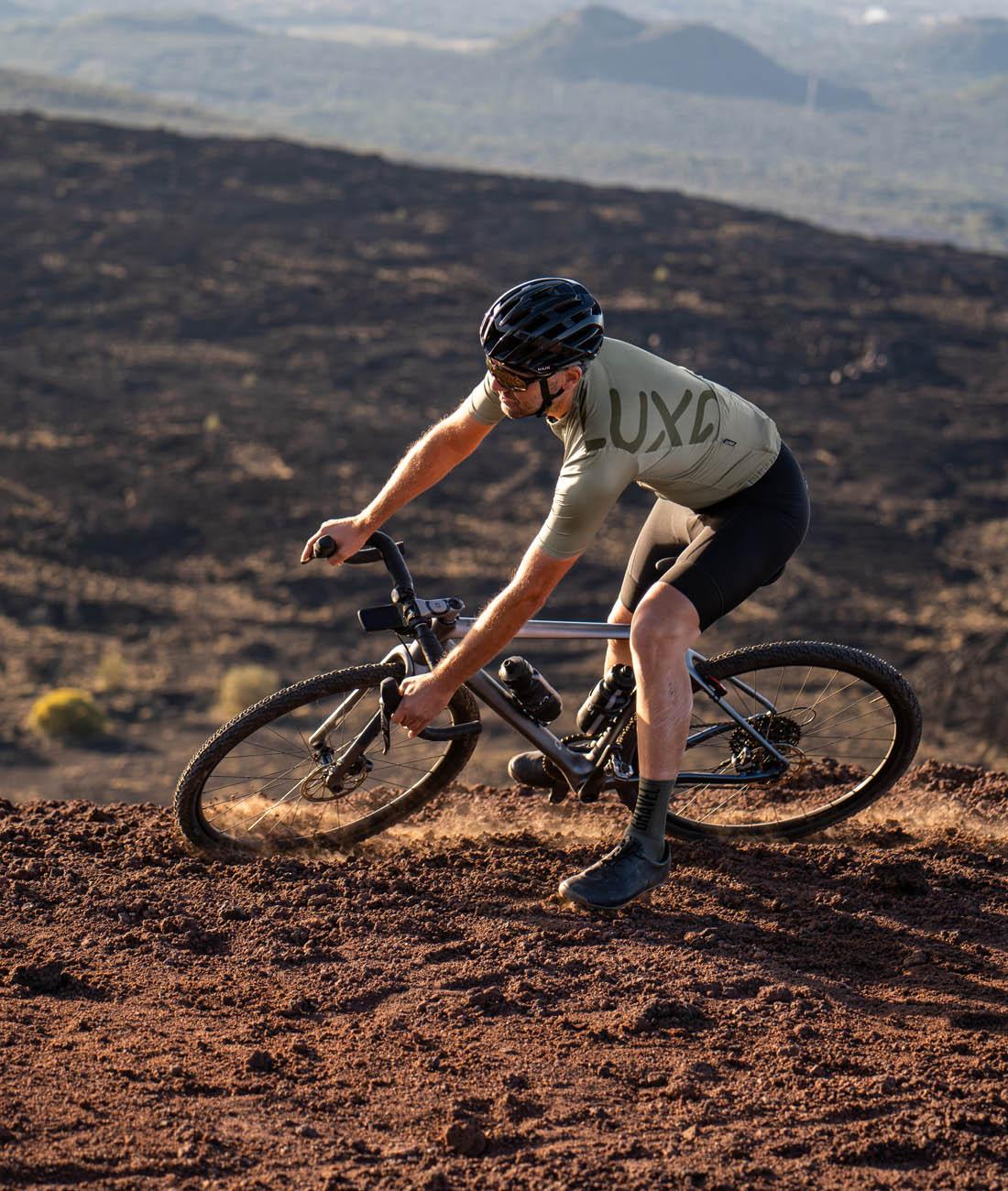 gravelowa przygoda na wulkanicznym szutrze pod wulkanem Etna na włoskiej wyspie Sycylia oraz kolarz ubrany w oliwkową koszulę polskiej marki Luxa