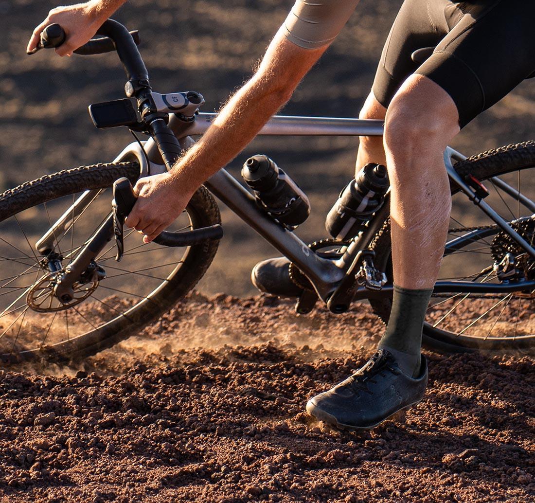 rower gravelowy rondo i kolarz skarpetkach khaki do jazdy gravelem marki Luxa