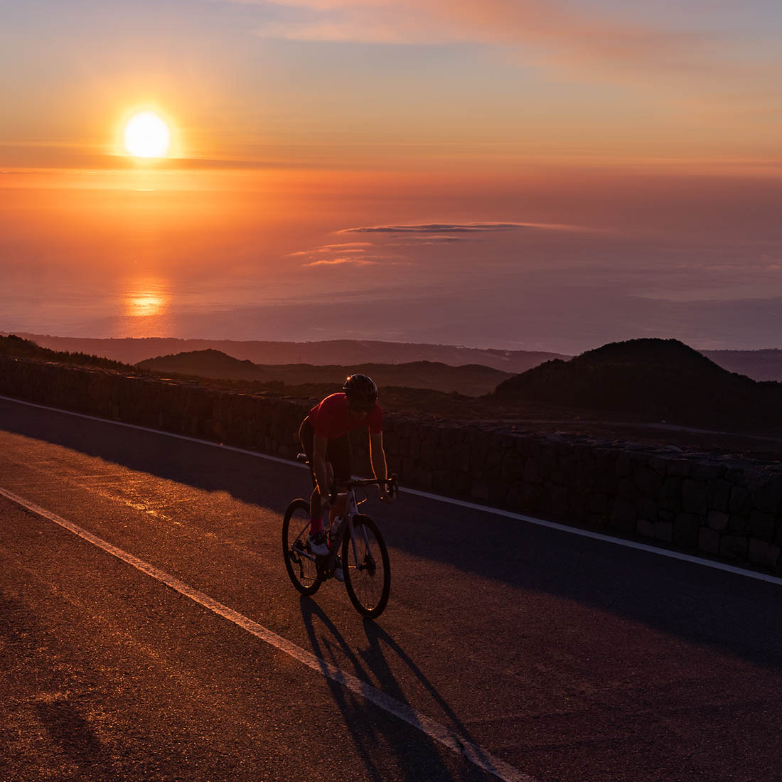 setting sun on Sicily (Etna) and Luxa cyclist on the road