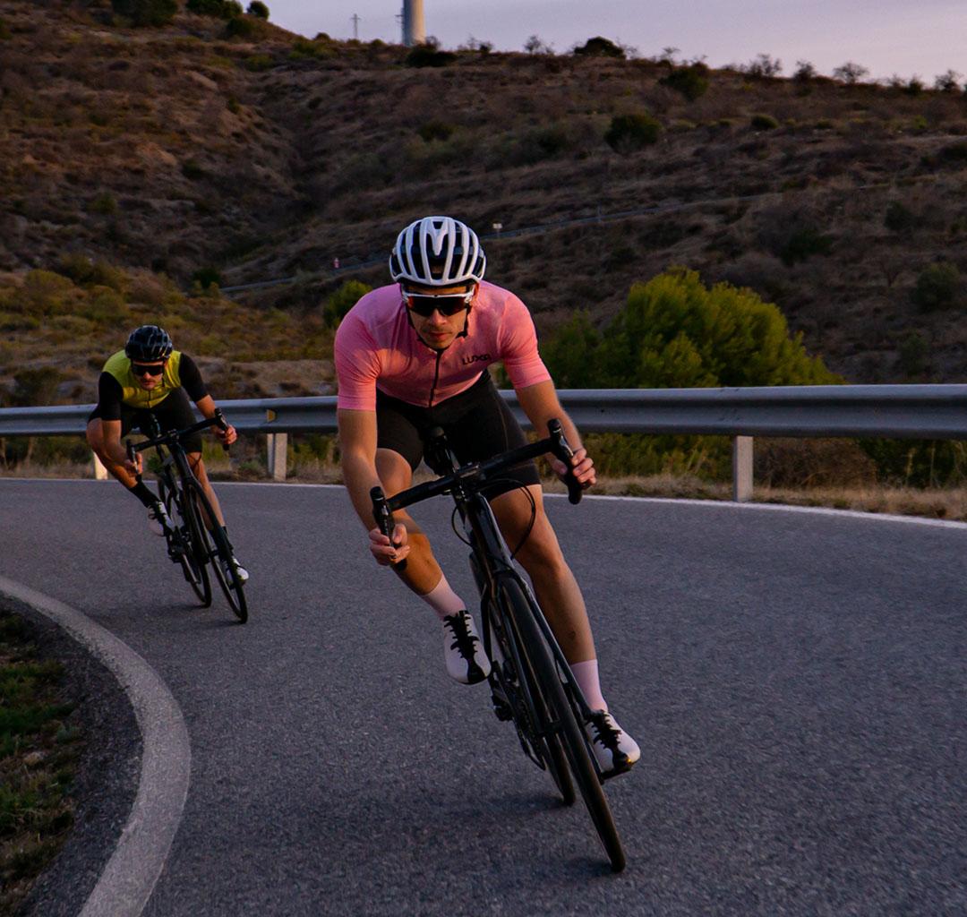 kolarze na szybkim zjeździe w różowej koszulce kolarskiej luxa