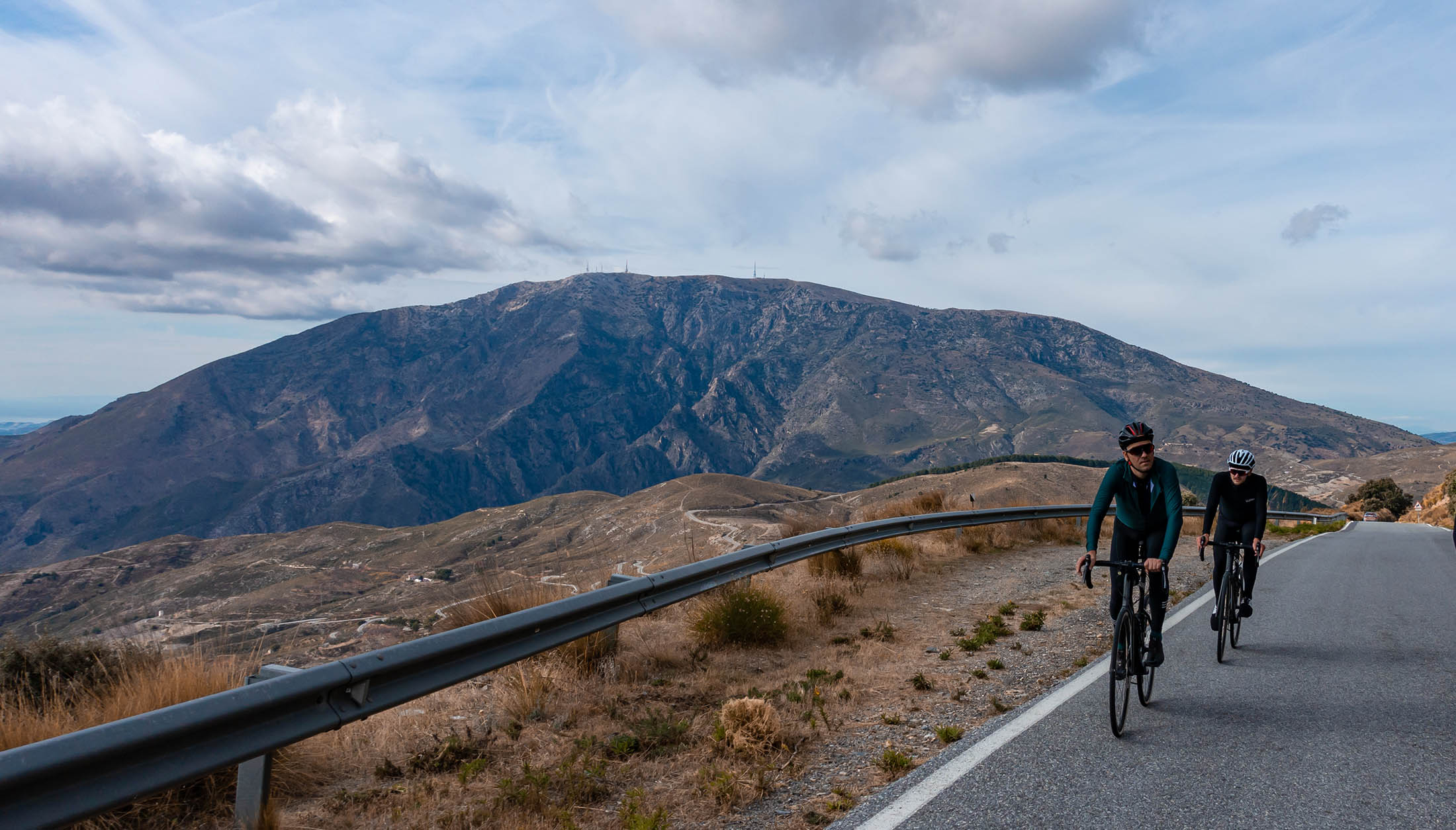 beautiful Andalusia roads in the Sierra Nevada. Two cyclists wear Luxa spring jackets