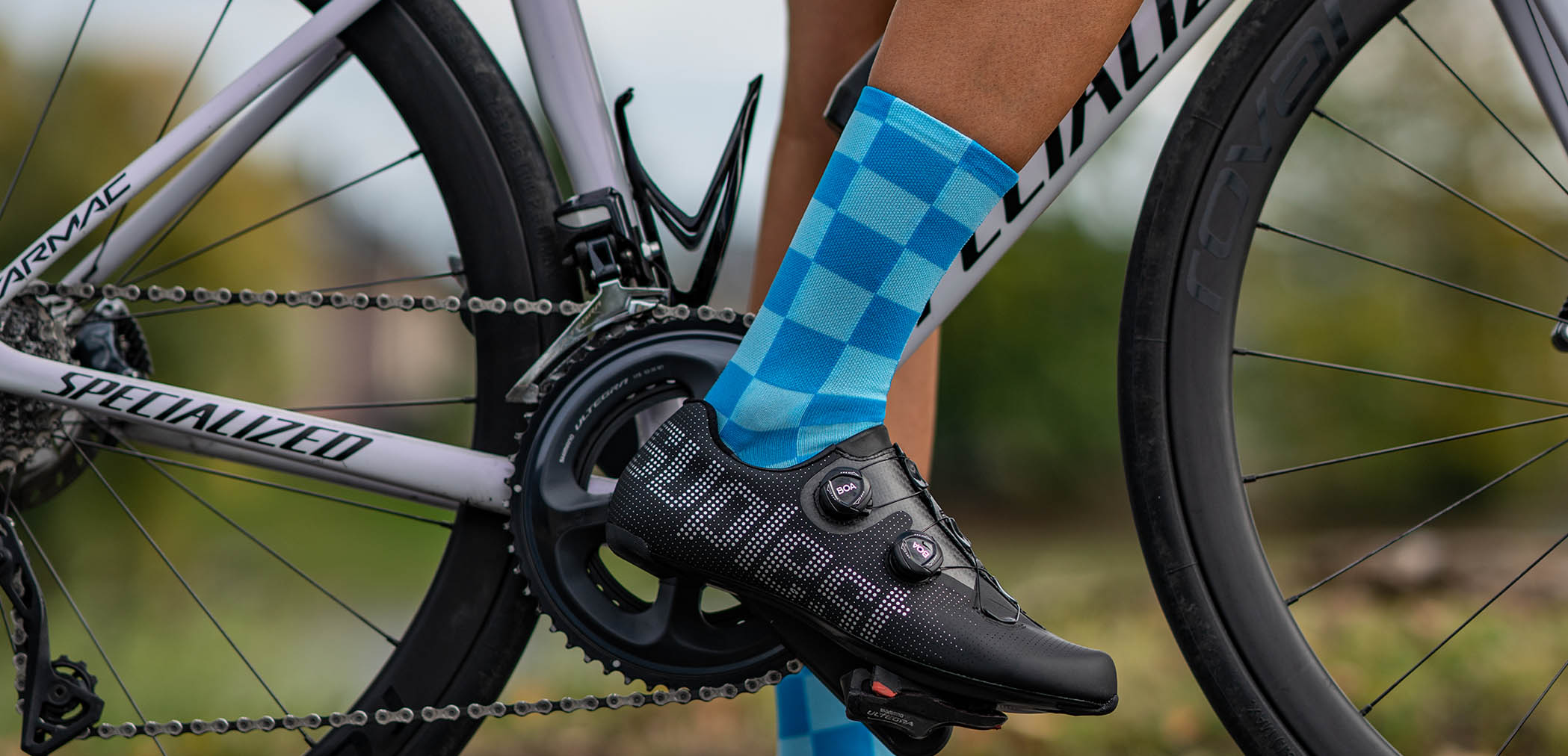 chequered pattern on the blue Luxa Squares cycling socks and suplest road shoes
