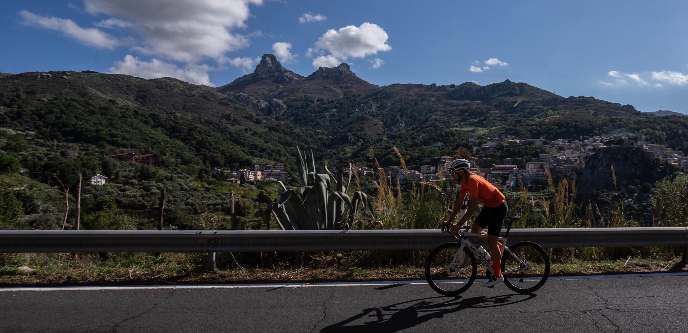 ubrany w pomarańczowy komplet stroju kolarskiego jedzie w czasie upalnej sycylijskiej temperatury
