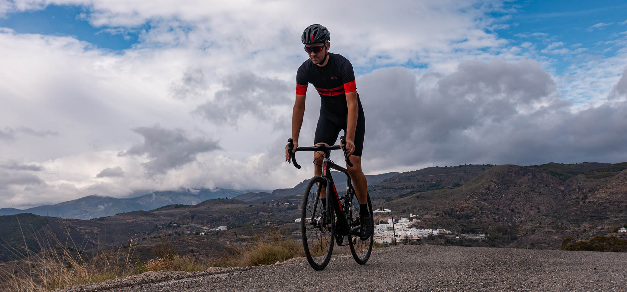 good grounds for cyclists in the mountains of Andalusia. Cyclist in a Luxa cycling jersey with red sleeves