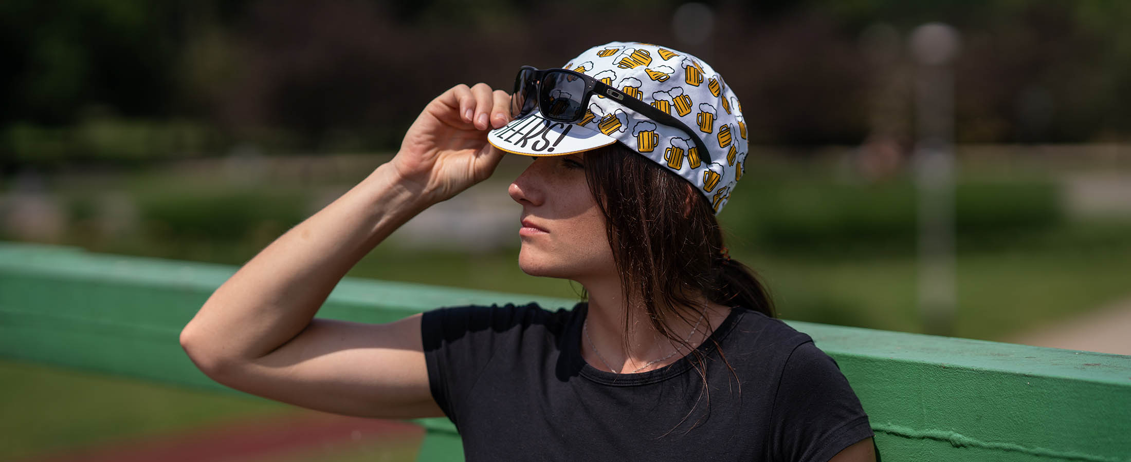 young female cyclist is wearing 'beer ride' cap