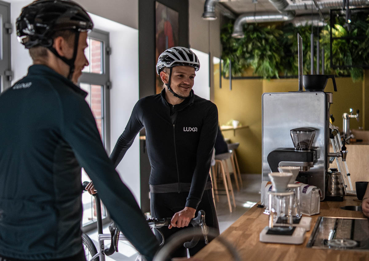 Two cyclists wear Luxa and order a coffee