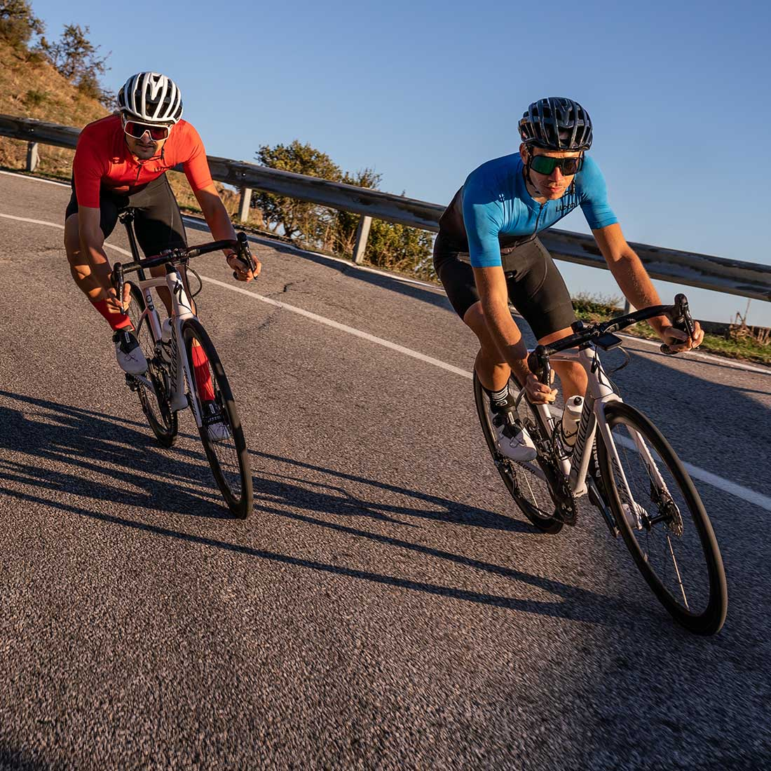 two road cyclists descending on Sicily road and wears luxa galaxy jerseys