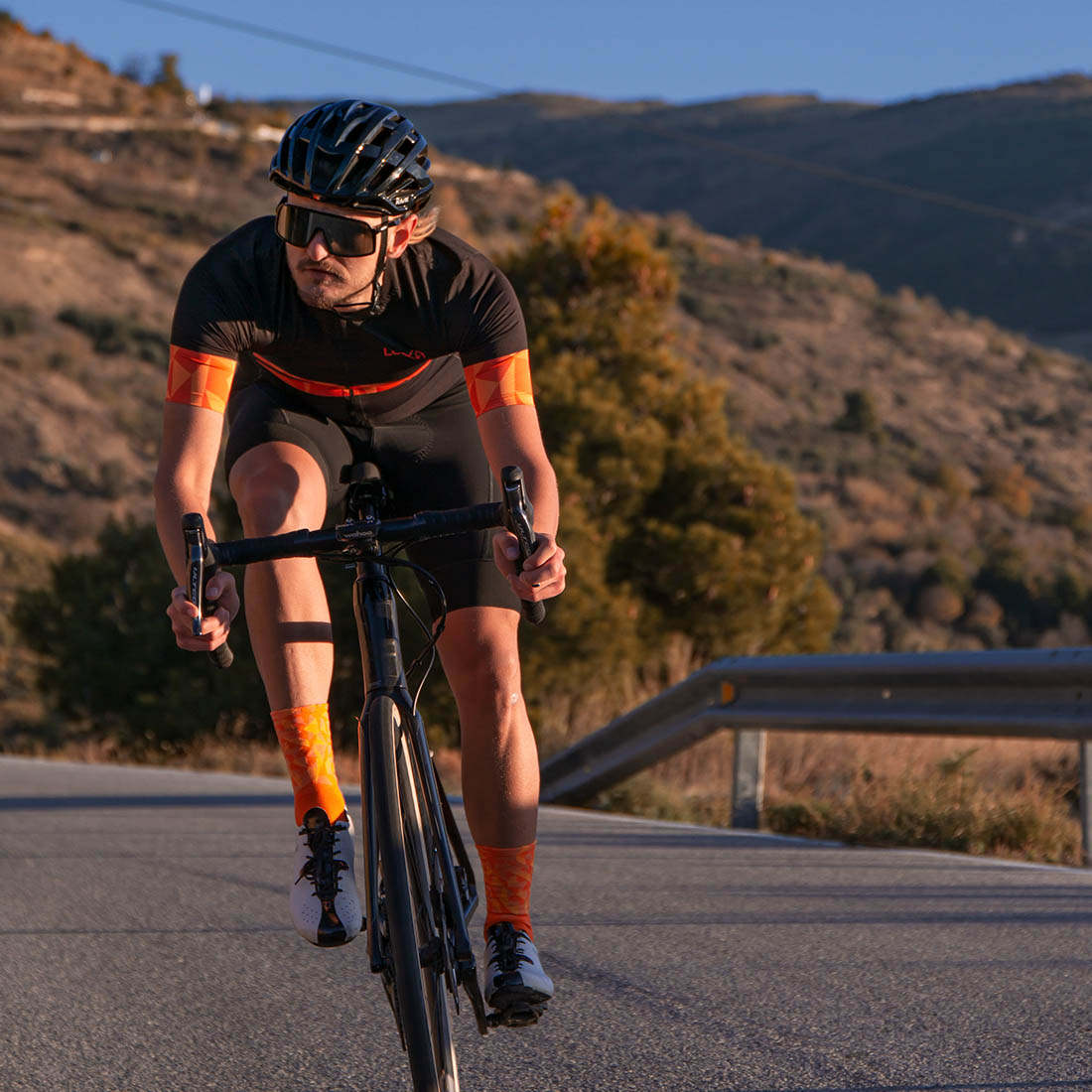 cyclist on the road with luxa warm orange jersey