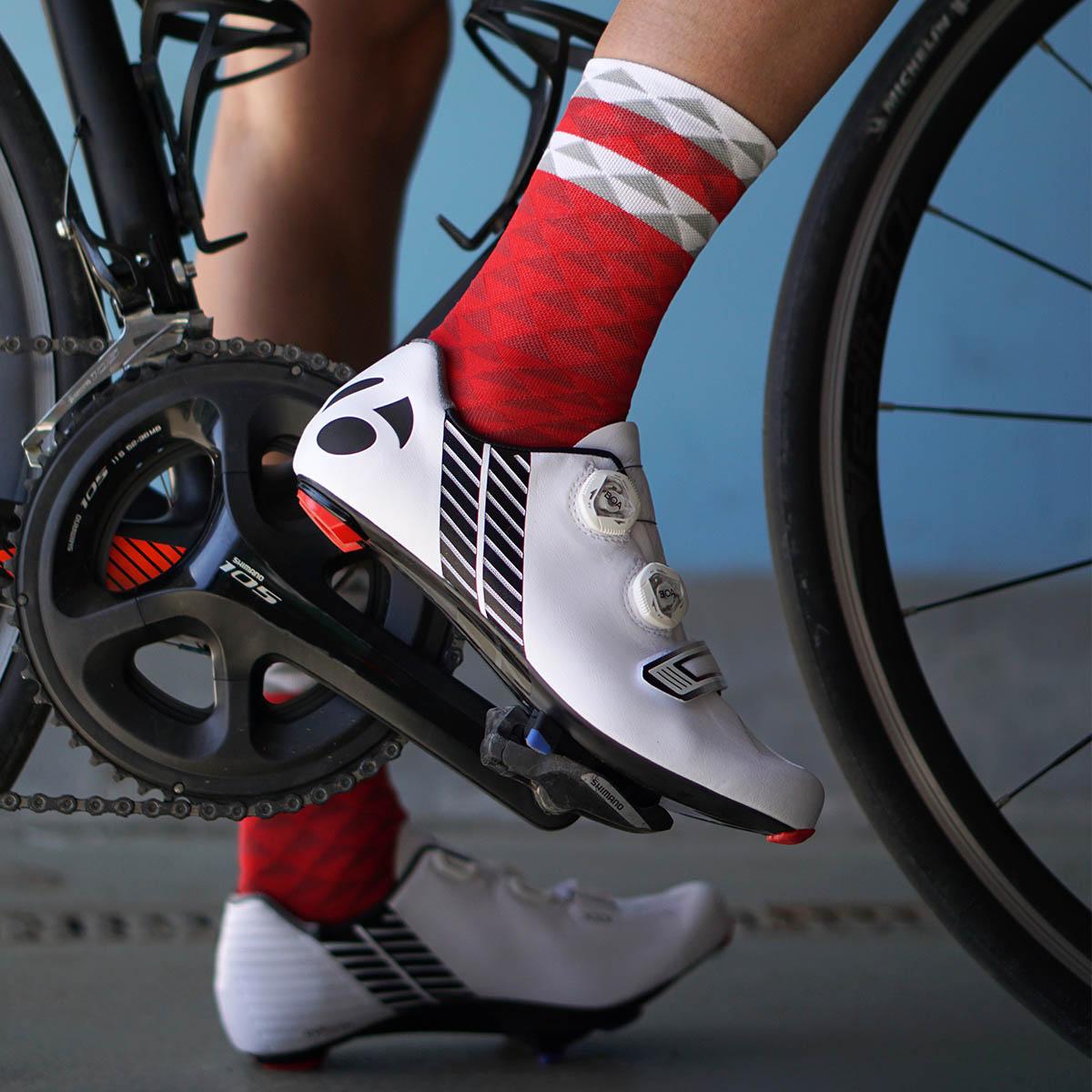 Noga kolarza i czerwone skarpety rowerowe Luxa Asymmetric Red. Rower szosowy Orbea i buty Bontrager